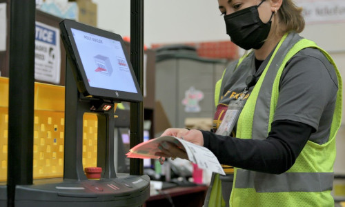 A warehouse worker for Superior Uniform Group scans a shipment label on a collaborative mobile robot from 6 River Systems at a facility in Coppell, Texas
